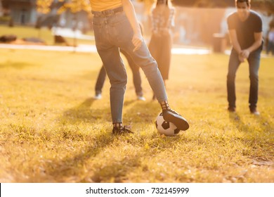 selective focus of friends playing soccer together in park