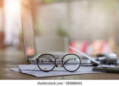 selective focus front eyeglasses on table with blur office supplies, vintage light tone.