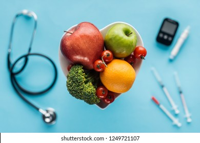 selective focus of fruits and vegetables in heart shaped bowl with medical equipment on blue background