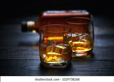 Selective focus glasses of cold whiskey on wooden table.Full bottle of whiskey