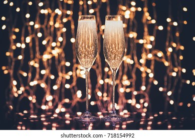 selective focus of glasses full of champagne against christmas lights
