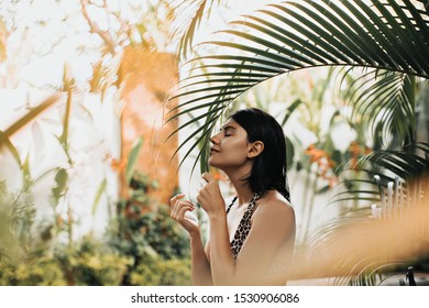 Selective focus of gorgeous girl with tattoo enjoying vacation. Brunette european lady touching palm tree leaf on nature background.
