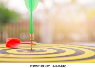 selective focus green dart hitting in target center of dartboard and falling red dart with orange lighting,competitive business concept,organization that has potential to be lead the business