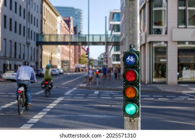 Selective focus, Green traffic light with bicycle symbol on sidewalk beside bicycle lane in Europe and defocus of people ride bicycle.