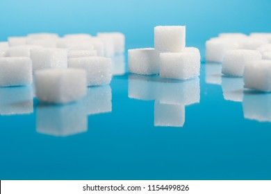 selective focus Group of Sugar cubes vary position on light blue background