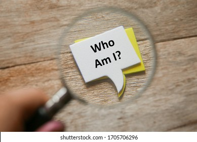 Selective focus of hand holding magnifying glass focusing a stack of speech bubbles written with question Who Am I? on a wooden background.