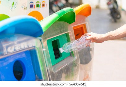Selective focus hand throwing empty plastic bottle into the trash