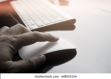 selective focus hand touching mouse and click with keyboard and electronic device for start up business working on darken background with soft flare