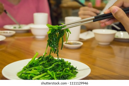 selective focus of hand using chopstick to eat stir fried morning glory serving on white plate in chinese restaurant.