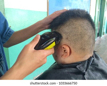 Selective focus of The hands of hairdresser is cutting hair for the boy in thai school rules.hair style,occupation concept.