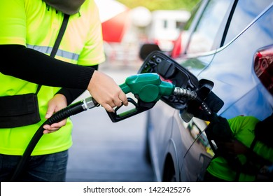 Selective focus to hands of staff, hands refilling the car with fuel at the gas  station, black car in gas station, refilling the car with fuel at the refuel station, the concept of fuel energy.