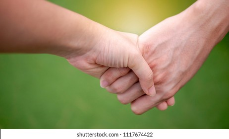 selective focus of hands while man and woman holding hand and walk together in the park with good moment.