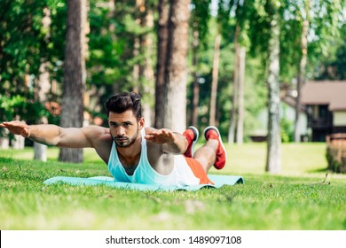 selective focus of handsome bearded man working out outside on lawn