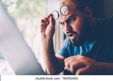 Selective focus, Handsome hipster guy correcting cool eyewear while checking results of favorite football team on laptop computer.Good looking male person seems surprised while reading news in webpage