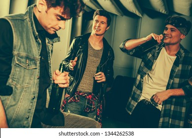 selective focus of handsome men holding bottles with beer while looking at friend