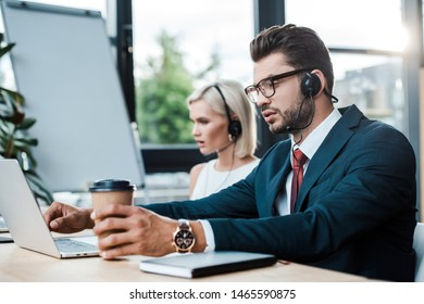 selective focus of handsome operator in headset holding coffee to go near laptop and blonde colleague in headset