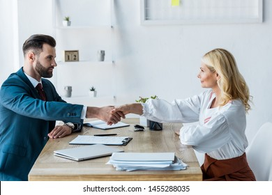 selective focus of handsome recruiter and attractive employee shaking hands