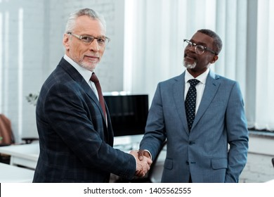 selective focus of happy businessman in glasses shaking hands with african american partner