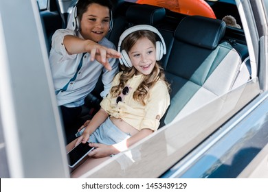 selective focus of happy kid pointing with finger near sister in headphones