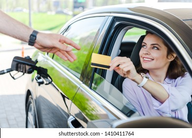 selective focus of happy woman sitting in car and giving credit card to worker at gas station