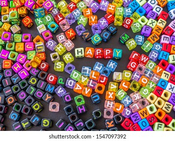 Selective focus at happy word with many multicolored and colorful of alphabet plastic box on black board background. Happiness concepts and ideas.