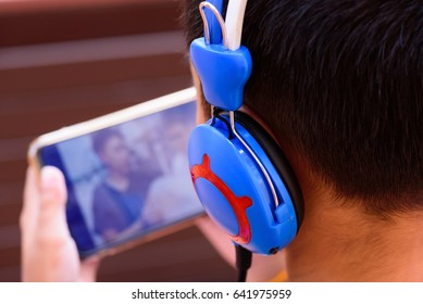 Selective focus headset of young boy listening and watching a movie in mobile phone.Happy and relaxation time for a children.