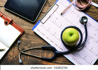 Selective focus Health care concept. Stethoscope and apple with medical chart,measuring tapes. effect light added.