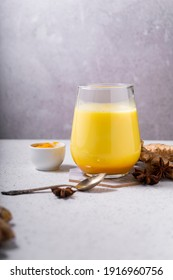 selective focus. Healthy ayurvedic drink golden almond milk or pumpkin turmeric latte with curcuma powder on white background. copy space.Trendy Asian natural detox beverage with spices for vegans