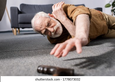 selective focus of helpless senior man fallen on floor and trying to get walking stick - Shutterstock ID 1778073032