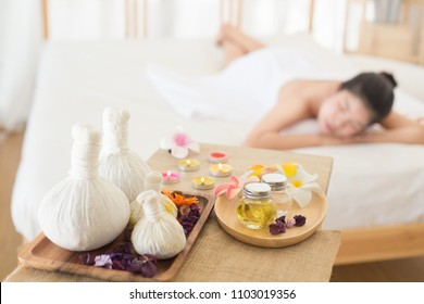 Selective focus of  Herbal compress balls with oil  on the wooden table in spa salon and blurred background of woman lying on bed.  alternative medicine and relaxation Concept.