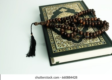 Selective focus of Holy Quran and rosary/tasbih isolated white background.