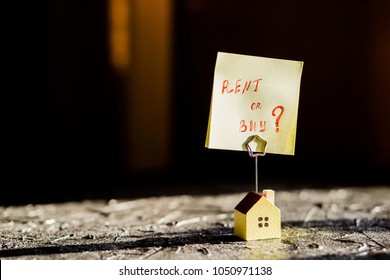 Selective focus of house model,poster , yellow sticker with notes written with 'BUY OR RENT?'. Real estate theme.Text message Buy or rent . Business concept