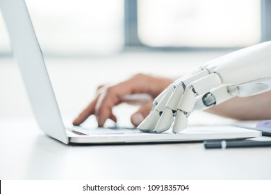 selective focus of human and robot hands typing on laptop at workplace