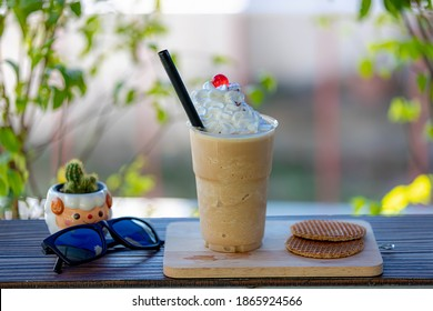 Selective focus of Iced coffee in plastic glass served with whipping cream and stroopwafel on the side, Iced coffee frappe on wooden plank with green garden as as background.