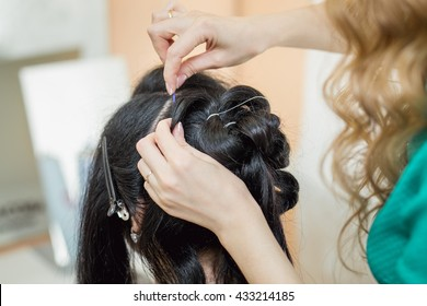 Selective focus image of beautiful hairdresser hands doing hairstyle to her client at hair salon.