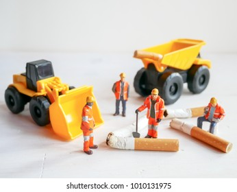 Selective focus image of cigarette butt and miniatures workers no smoking concept.  / with copy space