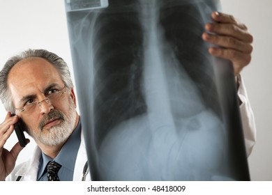 Selective focus image of a doctor wearing glasses and a white lab coat and looking intently at an x-ray while using his cell phone. Horizontal shot.