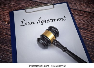 Selective focus image of gavel with Loan Agreement wording on a wooden background. Loan concept