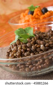 Selective focus image of a glass bowl with brown lentils.