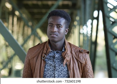 Selective focus image of a handsome young black man standing below girders of a bridge