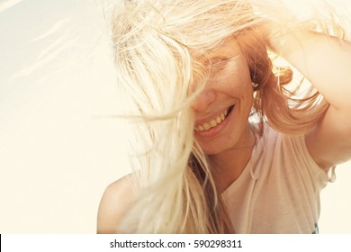 Selective focus image of happy girl face backlit by sunshine colorized vintage retro color filter.
