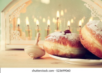 Selective focus image of jewish holiday Hanukkah with menorah (traditional Candelabra), donuts and wooden dreidel (spinning top)
