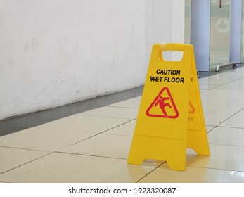 Selective focus image with noise effect shopping mall interior with wet floor caution sign.