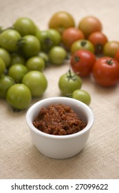 Selective focus image of tomato relish with green and red tomato relish in background.