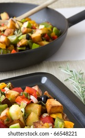 Selective focus image of a typical Greek pan-fried vegetables like pepper, olives, potatoes und zucchini.