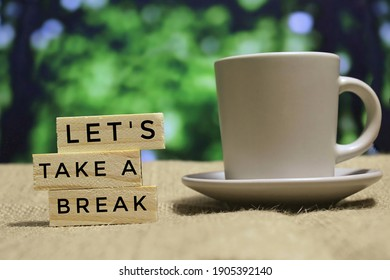 Selective focus image of wooden tiles with text LET'S TAKE A BREAK and cup of coffee. Bokeh effect background