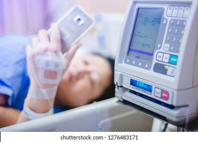 Selective focus to Infusion pumps with blurry patient play smart phone in hospital. The concept of working anytime.