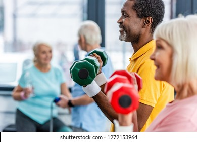 selective focus of interracial mature couple doing exercise with dumbbells at gym