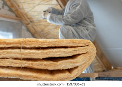 Selective focus of isolation material. Background with cropped view of professional foreman in protective workwear installing thermal insulation layer with fiberglass wool under the roof