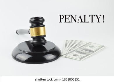 Selective focus of judge gavel and banknotes over white background written with text PENALTY!.